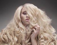 Nahaufnahmeporträt einer Blondine mit einer flaumigen, gelockten Frisur stockfoto