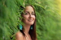 Nahaufnahmeporträt einer Frau in einer grünen Hecke des Grases stockfotografie