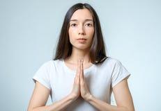 Nahaufnahmeporträt einer jungen betenden Frau Stockbild