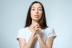 Nahaufnahmeporträt einer jungen betenden Frau Lizenzfreies Stockfoto