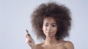 Nahaufnahmeporträt einer jungen Frau, die einen Lippenstift im Studio hält stock video