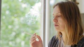 Nahaufnahmeporträt einer jungen Frau mit einer Zigarette stock video