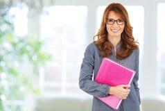 Lächelnde Geschäftsfrau, die im Büro steht Stockbild
