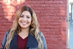 Nahaufnahmeporträt eines attraktiven Lächelns der jungen Frau Stockbild
