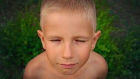 Nahaufnahmeporträt eines blauäugigen kleinen Jungen, der direkt der Kamera, ein piercing Blick eines 6-jährigen Kindes, Ansicht b stock video footage