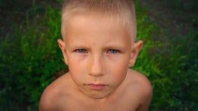 Nahaufnahmeporträt eines blauäugigen kleinen Jungen, der direkt der Kamera und den Versuchen betrachtet, um zu lächeln, ein pierc stock video