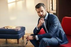 Nahaufnahmeporträt eines hübschen Geschäftsmannes in einer Klage, die auf Sofa im Büro sitzt und die Kamera betrachtet stockfoto
