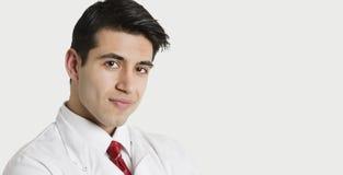 Nahaufnahmeporträt eines hübschen indischen männlichen Doktors, der über hellgrauem Hintergrund lächelt Lizenzfreies Stockfoto