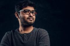 Nahaufnahmeporträt eines jungen indischen Kerls im Eyewear und in zufälliger Kleidung, die eine Kamera im Studio betrachten lizenzfreie stockfotografie