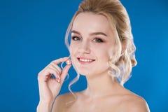 Nahaufnahmeporträt eines jungen Mädchens auf einem blauen Hintergrund lizenzfreies stockfoto