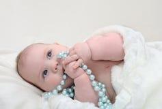 Entzückendes kleines Baby mit den Perlen, die beiseite schauen Lizenzfreie Stockfotos
