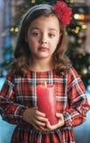 Nahaufnahmeporträt eines netten, kleinen Mädchens, das eine Kerze hält stockbild
