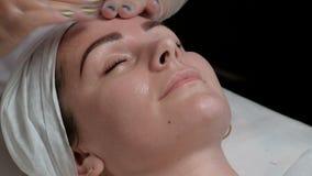 Nahaufnahmeporträt eines schönen Mädchens in einem BADEKURORT-Salon Massieren Sie das Gesicht mit einer Ernährungs- oder Reinigun stock video