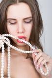 Nahaufnahmeporträt eines schönen Mädchens mit den roten Lippen, eine Perlenhalskette halten der offene Mund, perlt Noten ihre Lip Stockbild