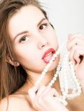 Nahaufnahmeporträt eines schönen Mädchens mit den roten Lippen, eine Perlenhalskette halten der offene Mund, perlt Noten ihre Lip Stockfotografie