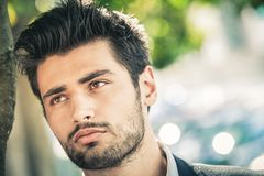 Nahaufnahmeporträt eines schönen und attraktiven Mannes mit einem Bart und einem modischen Haar stockbild