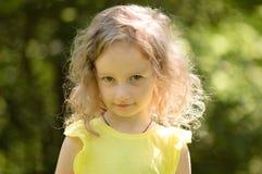 Nahaufnahmeporträt eines skeptischen kleinen Mädchens, das misstrauisch, skeptisch, Halblächeln, ironisch schaut Portrait im Grün stockfoto