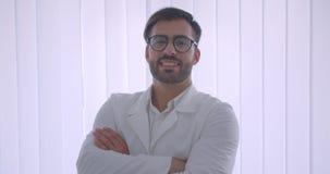Nahaufnahmeporträt erwachsenen hübschen kaukasischen männlichen Doktors in den Gläsern mit seinen Armen gekreuzt über dem Kasten, stock footage