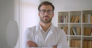 Nahaufnahmeporträt erwachsenen hübschen kaukasischen männlichen Doktors im weißen Mantel und in den Gläsern, die Kamera in der Bi stock video footage