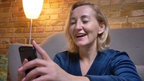 Nahaufnahmeporträt froher älterer kaukasischer Dame, die in Smartphone aufpasst und in der gemütlichen Hauptatmosphäre lacht lizenzfreie stockfotos