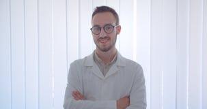 Nahaufnahmeporträt jungen hübschen kaukasischen männlichen Doktors, der die Kamera glücklich lächelt mit seinen Armen betrachtet, stock video footage