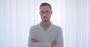 Nahaufnahmeporträt jungen hübschen kaukasischen männlichen Doktors, der Kamera mit seinen Armen gekreuzt über Kasten im Weiß betr stock footage