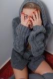 Nahaufnahmeporträt lustiger schöner blonder junger Dame, die den Spaß playfully versteckt Gesicht hinter Handdem glücklichen Läch Stockbild