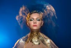 Nahaufnahmeporträt-Mädchenmodell in einer stilvollen Goldfolie Lizenzfreie Stockfotografie