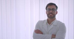 Nahaufnahmeporträt männlichen Doktors des erwachsenen hübschen bärtigen Kaukasiers in den Gläsern mit seinen Armen gekreuzt über  stock footage