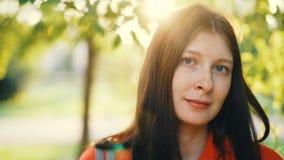 Nahaufnahmeporträt reizend junger Dame, die die Kamera steht im Park am sonnigen und windigen Tag lächelt und betrachtet Gesund stock video footage
