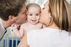 Nahaufnahmeporträt von den jungen Eltern, die schönen neugeborenen Sohn küssen lizenzfreies stockbild