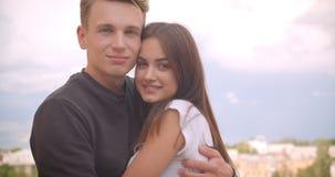Nahaufnahmeporträt von den jungen netten kaukasischen Paaren, die Kamerastellung auf dem Balkon ihres Hauses mit betrachtend umar stock video
