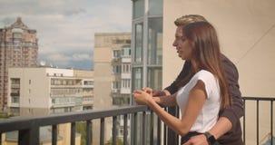 Nahaufnahmeporträt von den jungen netten kaukasischen Paaren, die schöne Landschaftsstellung auf dem Balkon ihres Hauses betracht stock footage