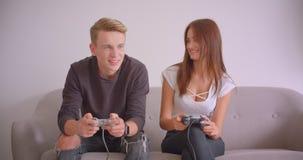 Nahaufnahmeporträt von den jungen netten kaukasischen Paaren, welche die Videospiele zusammen zuhause sitzen auf der Couch in spi stock video footage