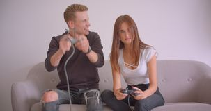 Nahaufnahmeporträt von den jungen netten kaukasischen Paaren, welche die Videospiele zusammen zuhause sitzen auf der Couch in spi stock footage