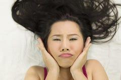 Nahaufnahmeporträt von den schwermütigen asiatischen Frauen, die auf dem Boden mit dem schwarzen langen Haar liegen umgekippt f stockbilder
