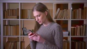Nahaufnahmeporträt von jungen attraktiven Studentingrasen socail Medien am Telefon und Betrachten der Kamera in stock footage