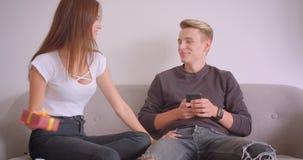 Nahaufnahmeporträt von jungen netten kaukasischen Paaren zuhause in der Wohnung Mann unter Verwendung des Telefons, das auf der C stock video footage
