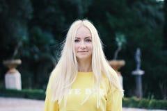 Nahaufnahmeporträt von jungen schönen Blondinen mit grüner Parkanlage auf Hintergrund Wegkonzept Junge Erwachsene lizenzfreie stockfotografie