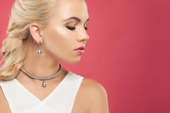 Nahaufnahmeporträt von perfekten Blondinen mit luxuriösen Platinschmuckohrringen und -halskette mit Diamanten und schwarzen Perle stockbilder