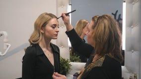 Nahaufnahmeporträt von schönen Blondinen Make-up unter Verwendung der Make-upbürste tuend stockbild