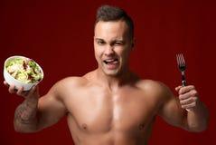 Nahaufnahmeporträt von starken muskulösen Athletenmännern mit dem neuen lächelnden Blinzeln des Salats und der Gabel Stockbild