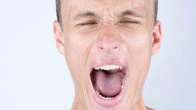 Nahaufnahmeporträt von verärgertem, Umkippen, depressesd, junger schreiender Mann lizenzfreies stockbild