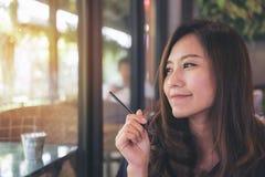 Nahaufnahmeporträtbild einer schönen Asiatin mit dem smileygesicht, das im modernen Café beim Denken an Geschäft sitzt Stockbild