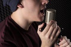 Nahaufnahmeporträtlippen emotional, den jungen Kerl singend, der vor dem Mikrofonstand hält seine Hände steht Lizenzfreies Stockbild