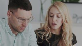 Nahaufnahmeporträttrieb des Mannes und der weiblichen Designer bei der Arbeit Sie sind ernst und auf das Lösen von wichtigen Prob stock video footage