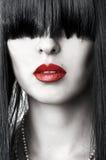 Nahaufnahmeportrait des Frauengesichtes mit den roten Lippen Stockfotografie