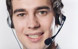 Nahaufnahmeportrait des jungen lächelnden Geschäftsmannes mit Kopfhörer Stockbild