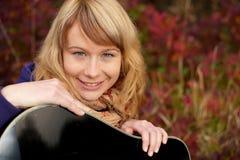 Nahaufnahmeportrait eines glücklichen jungen Mädchens mit Gitarre Lizenzfreies Stockbild