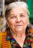 Nahaufnahmeportrait von einer zufriedenen älteren Frau Lizenzfreie Stockfotos
